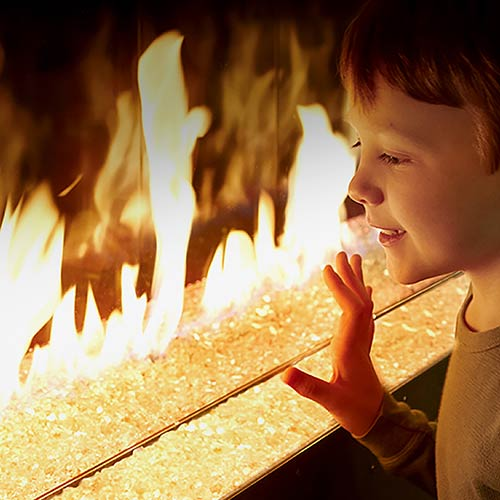 photo of boy touching fireplace glass